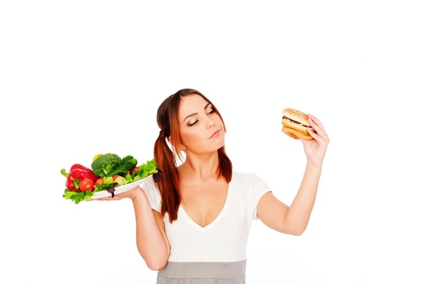 Девушка держит бутерброд и овощи