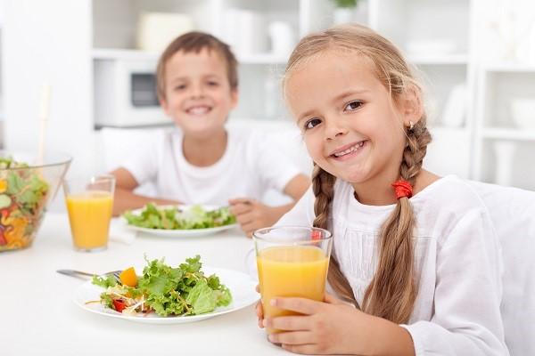 Мальчик и девочка кушают полезную еду на кухне
