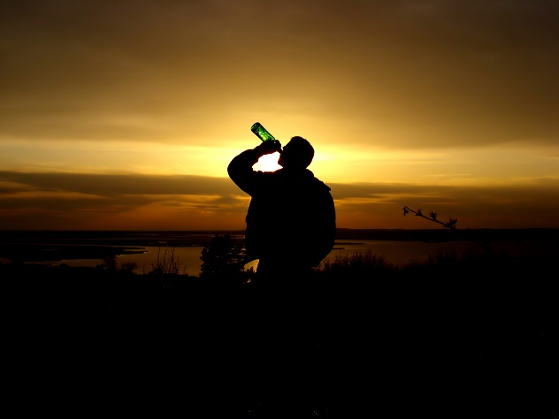 Мужчина пьет алкоголь из бутылки на фоне заката