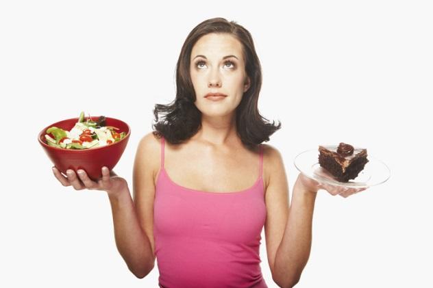 Женщина выбирает между полезной и вредной пищей
