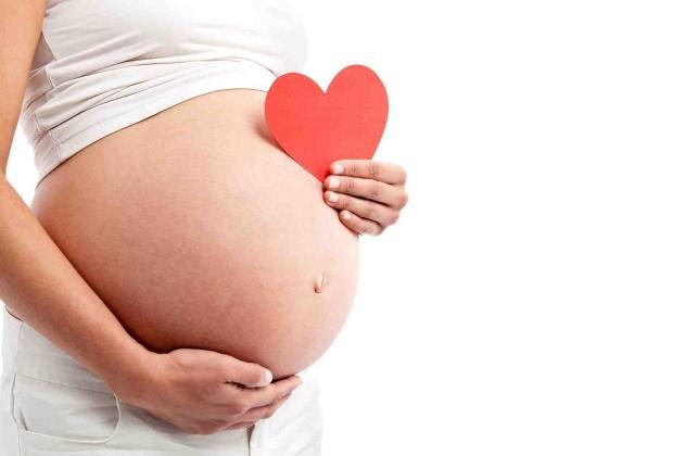 Беременная женщина в белой одежде держит красное бумажное сердечко