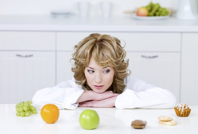 Девушка сидит за столом и выбирает что бы поесть