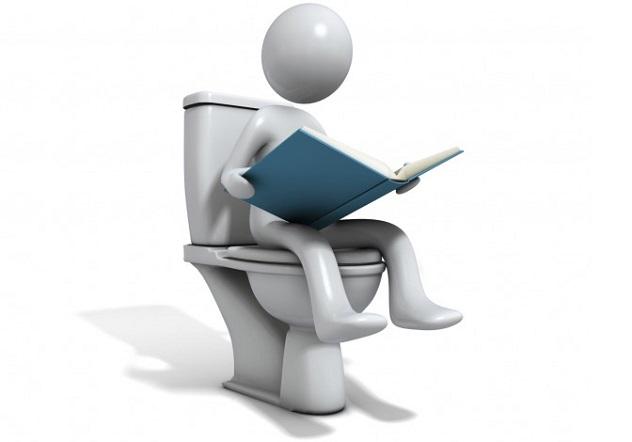 Человек сидит на унитазе и читает книгу