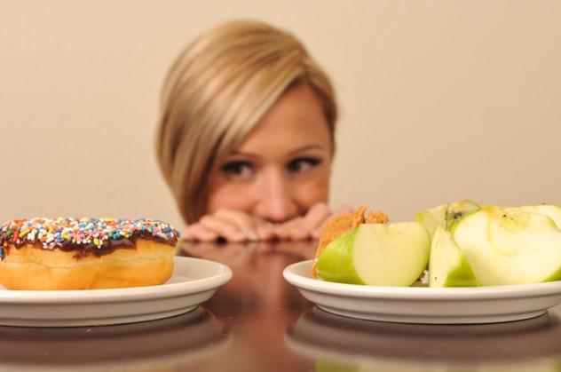 Девушка выбирает между полезной и вредной пищей