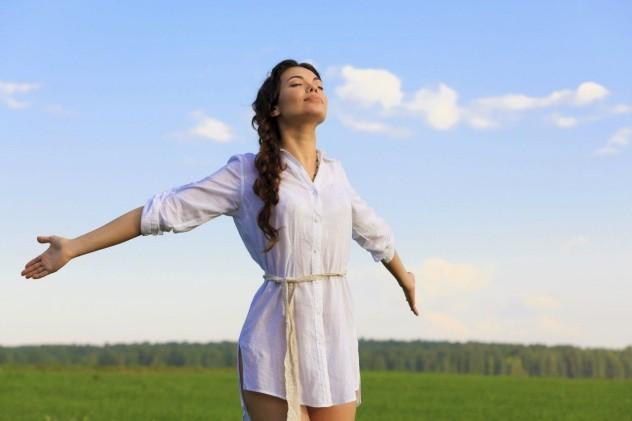 Девушка стоит на поле разведя руки в стороны
