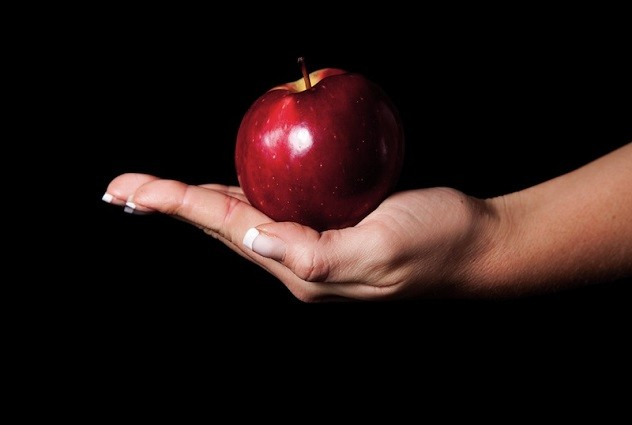 Женщина в руке держит яблоко