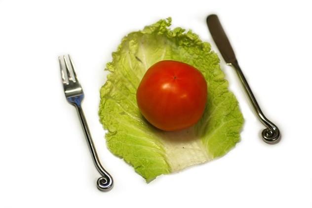 Помидор на листе капусты, вилка и ложка