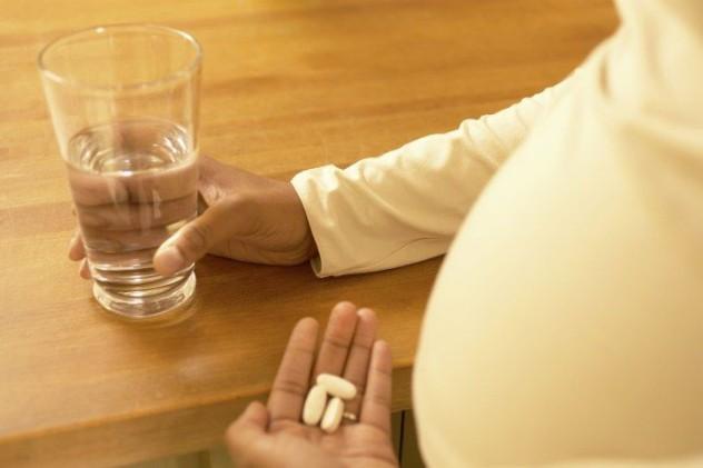 Беременная женщина собирается выпить таблетки