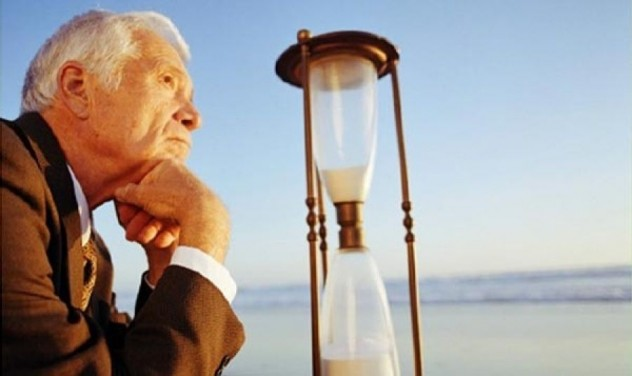 Мужчина пожилой смотрит на песочные часы