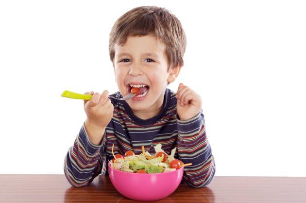 Мальчик ест салат