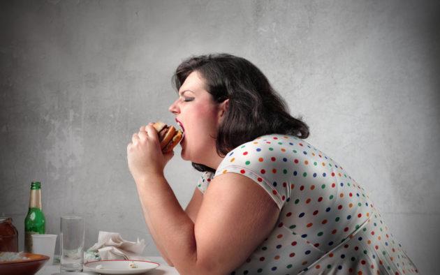 Полная женщина, страдающая гепатозом, ест гамбургер
