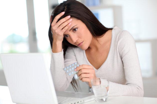 Женщина держит в руке таблетки от неспецифического язвенного колита